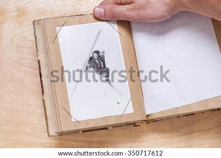 man holding a photo album with old photos