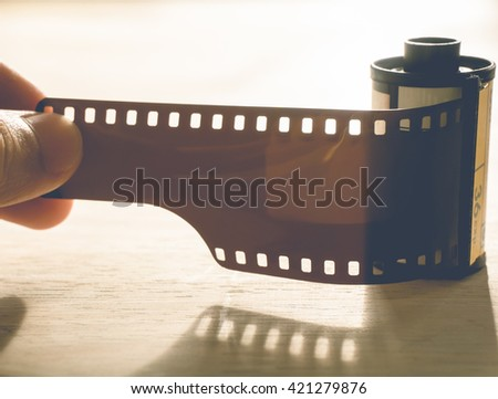 man holding a photo film cartridge  - vintage style