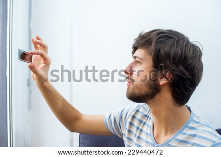 Man holding a piece of negative of a film in his hand and inspecting it.