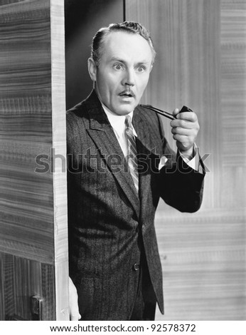 Man holding a pipe and standing at a doorway looking very surprised - stock photo