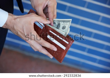 man holding a purse with money closeup