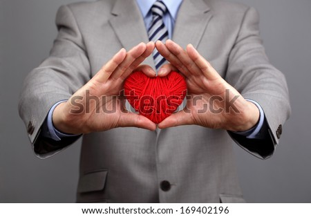 Man holding a red woolen heart concept for valentine's day, business customer care, charity, social and corporate responsibility - stock photo