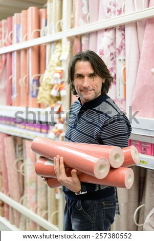 man holding a roll of a wallpaper in the store - stock photo