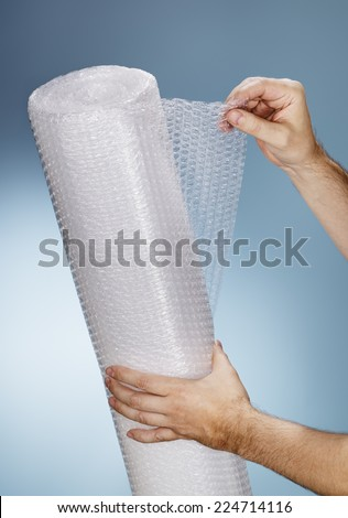 Man holding a roll of plastic bubble wrap. - stock photo