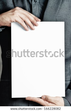 man holding a sheet of paper - stock photo