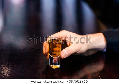 Man holding a shot on counter in a bar