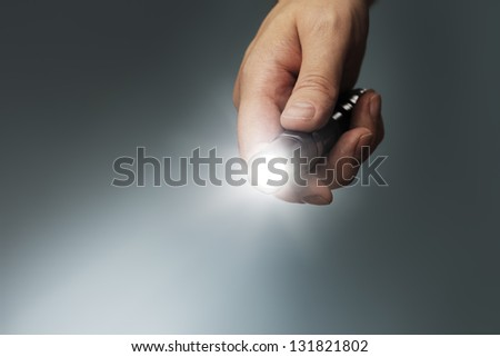 Man holding a small but powerful led flashlight in his hand. - stock photo