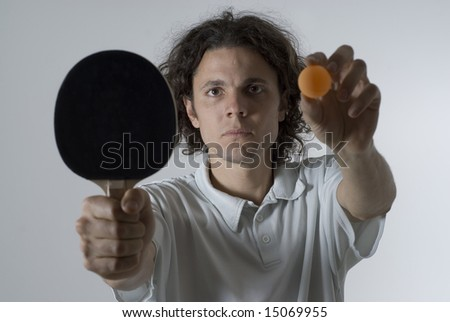 Man holding a table tennis ball and paddle out in front of him with a serious look on his face. Horizontally framed photograph - stock photo