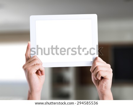 Man holding a tablet pc with blank screen in a house on background - stock photo