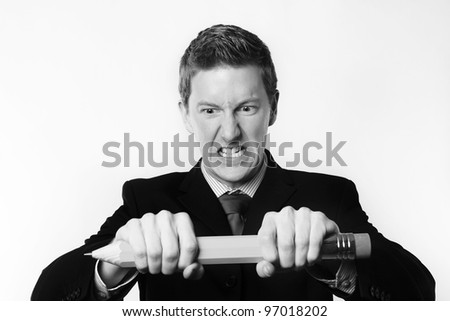 man holding a very large pencil trying to break it in two
