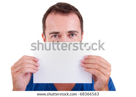 Man holding a white card in front of face, looking to camera, isolated on a white background. Studio shot.