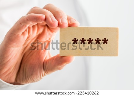 Man holding a wooden block with five stars denoting top or premium rating or quality, close up of his hand. - stock photo