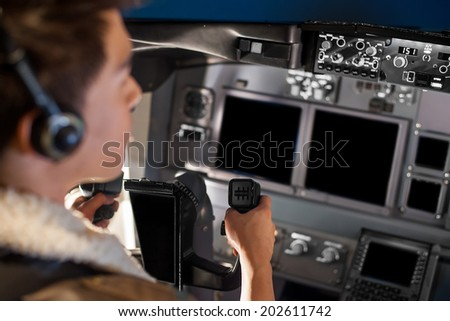 man holding airplane wheel in cockpit