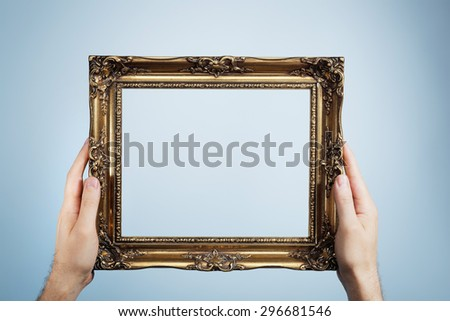 Man holding an antique look golden picture frame in his hands. - stock photo