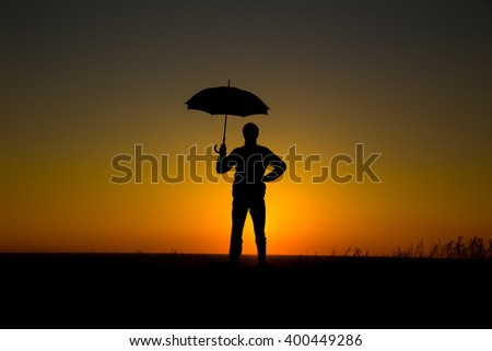 Man holding and umbrella in silhouette against  orange sunset