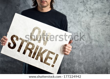 Man holding banner with ON STRIKE printed protest message. - stock photo