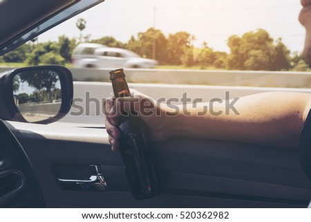 Man holding beer bottle while driving a car