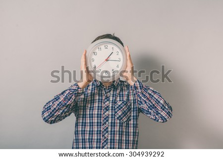 man holding big clock