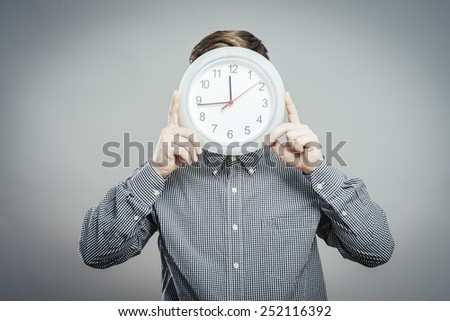 man  holding big clock covering his face over white