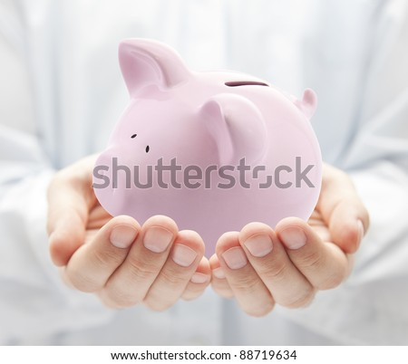 Man holding big pink piggy bank - stock photo