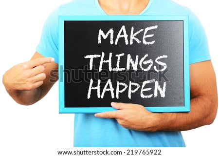 Man holding blackboard in hands and pointing the word MAKE THINGS HAPPEN