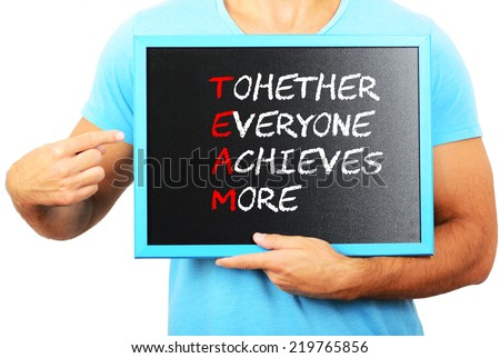 Man holding blackboard in hands and pointing the word TEAM - stock photo