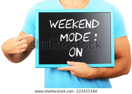Man holding blackboard in hands and pointing the word WEEKEND MODE : ON - stock photo