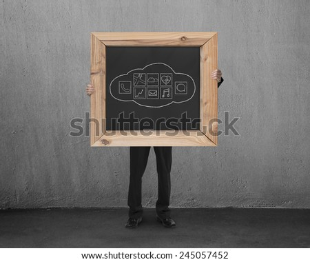 Man holding blackboard with hand-drawn cloud app icons in concrete room background - stock photo