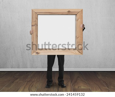 man holding blank whiteboard with wooden frame on concrete wall and wood floor background - stock photo