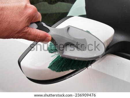 Man holding brush to clean car mirror - stock photo