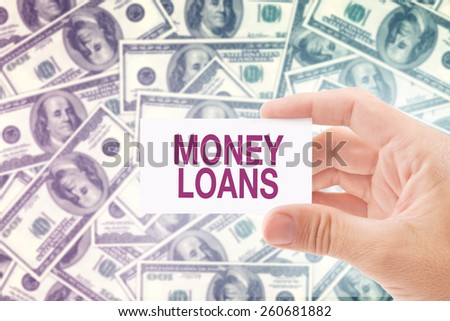 Man Holding Business Card with Money Loan Title, Dollar Banknotes Pile in The Background. Loan Shark Concept. - stock photo