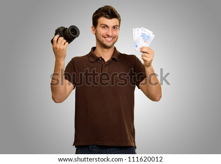 Man Holding Camera And Money On Gray Background