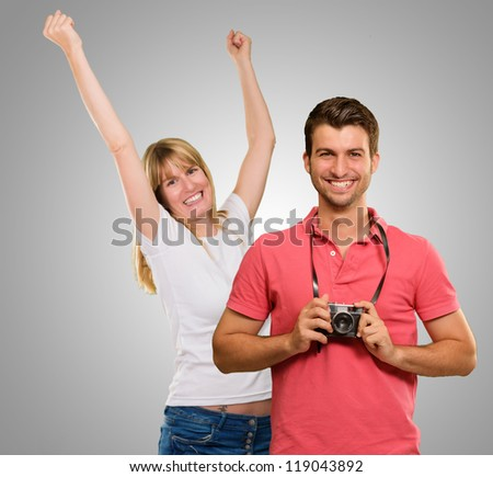 Man Holding Camera In Front Of Dancing Woman On Gray Background