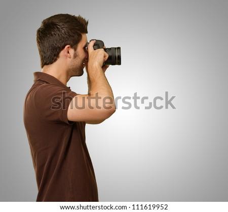 Man Holding Camera On Gray Background - stock photo