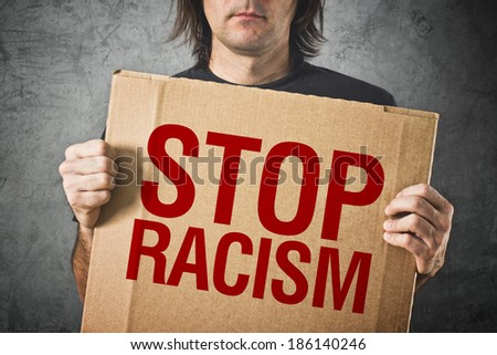 Man holding cardboard banner with STOP RACISM message - stock photo