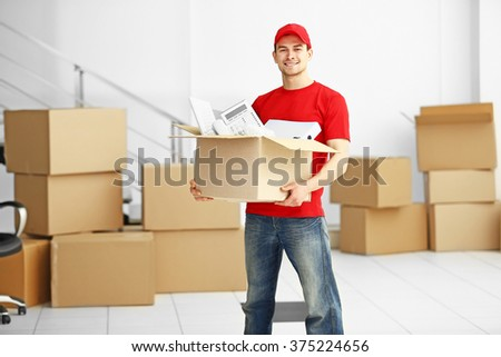 Man holding carton box full of office stationery in the room, close up - stock photo