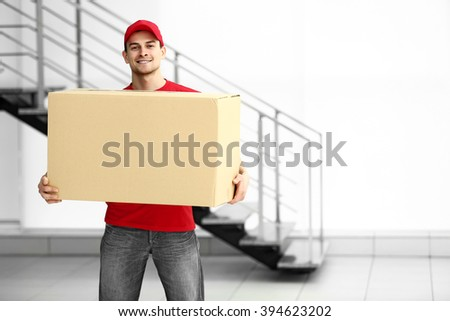 Man holding carton box in the room - stock photo