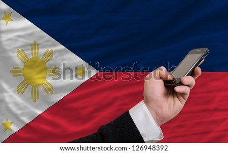man holding cell phone in front national flag of philippines symbolizing mobile communication and telecommunication - stock photo