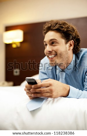 Man holding cellphone and lying on bed, relaxed. Looking away - stock photo