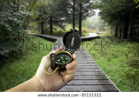 man holding compass with two paths ahead - stock photo
