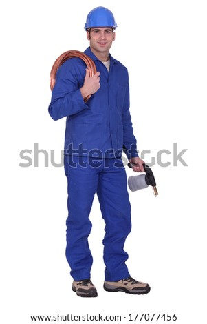 Man holding copper piping and blowtorch - stock photo