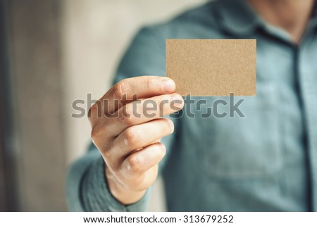 Man holding craft business card on concrete wall background - stock photo