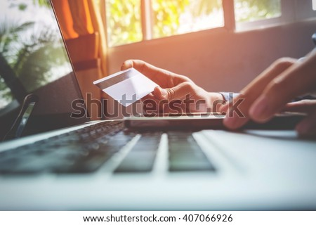 Man holding credit card in hand and entering security code using smart phone on laptop keyboard, online shopping concept. - stock photo