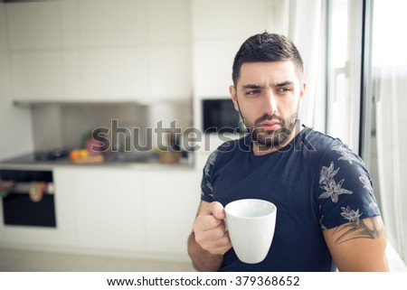 Man holding cup of hot beverage,coffee or tea.Enjoying his morning coffee in the kitchen.Looking trough the window.Thinking.Worried pensive man stress relief.Modern entrepreneur.New day starting.Ideas - stock photo