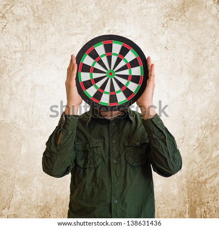 Man holding dartboard target in place of head.