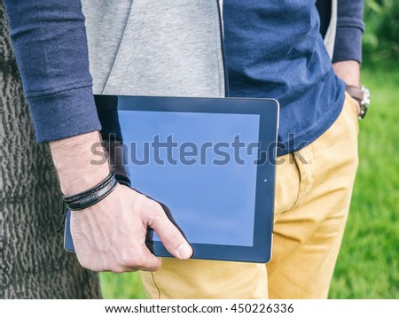 Man holding digital tablet with blank screen in hand