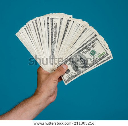 Man holding dollar bills on a blue background