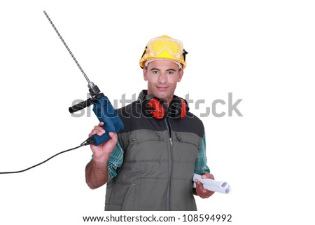 Man holding drill and plans - stock photo