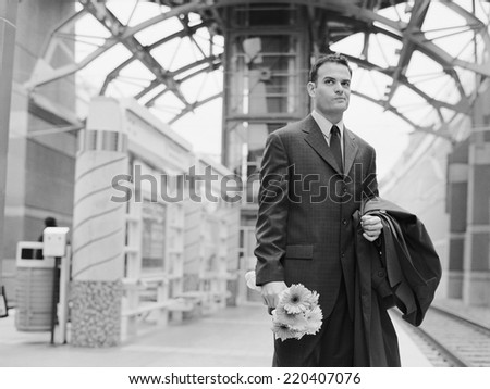 Man holding flowers and waiting at train station - stock photo