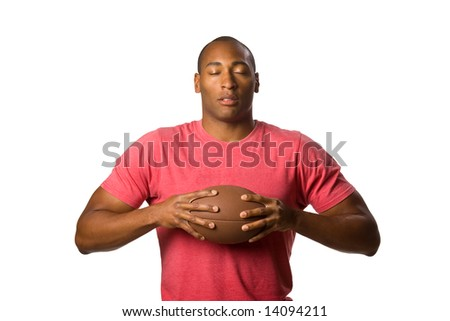Man holding football eyes closed in wishful state of mind. On-White